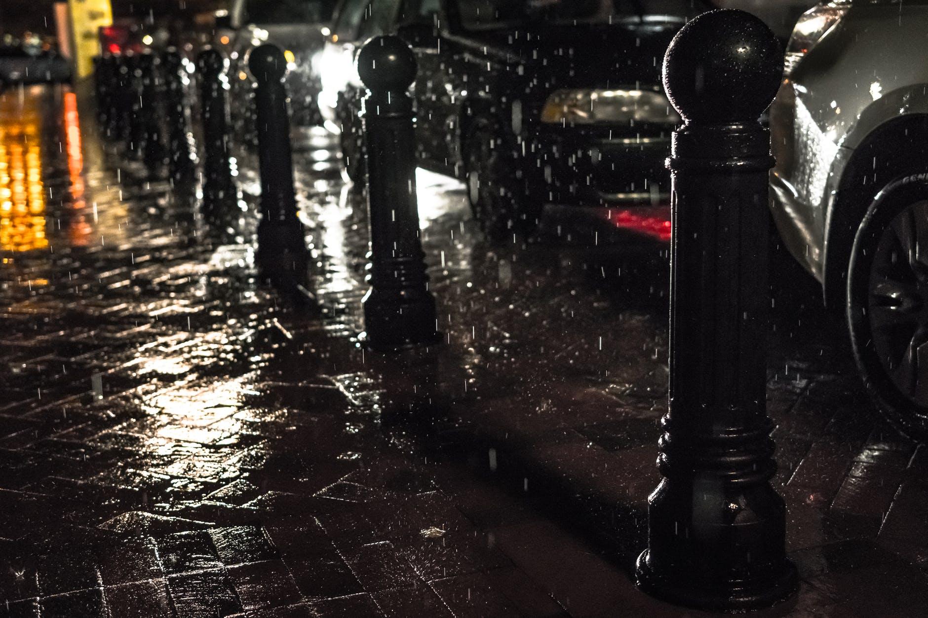 black posts on black pavement beneath falling rain